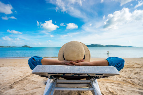 person relaxing on lounge chair on the beach enjoying benefits of a vacation