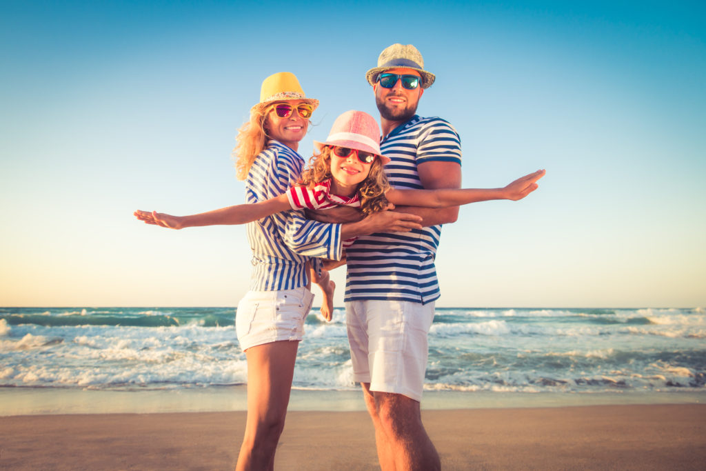 family of three enjoying benefits of a vacation on the beach