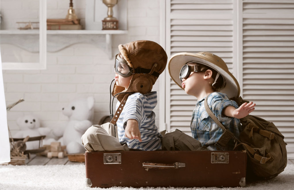 childhood best friends playing dress up and airplane with toys