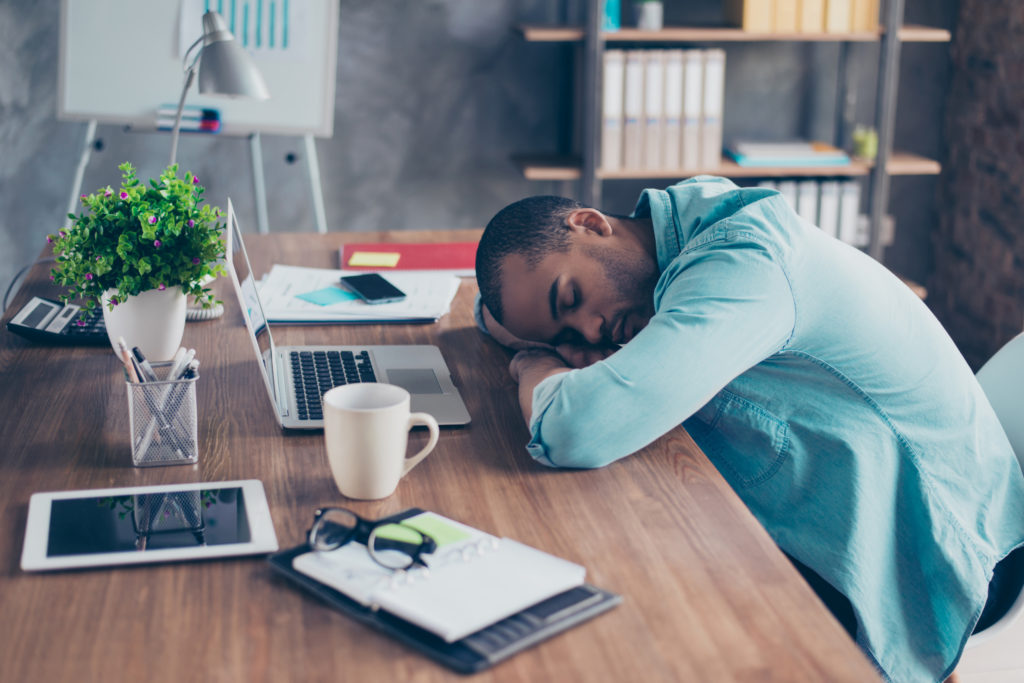 man with his head down at his desk suffering from chronic fatigue syndrome
