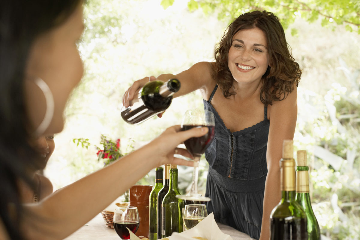 woman pouring red wine smiling with teeth