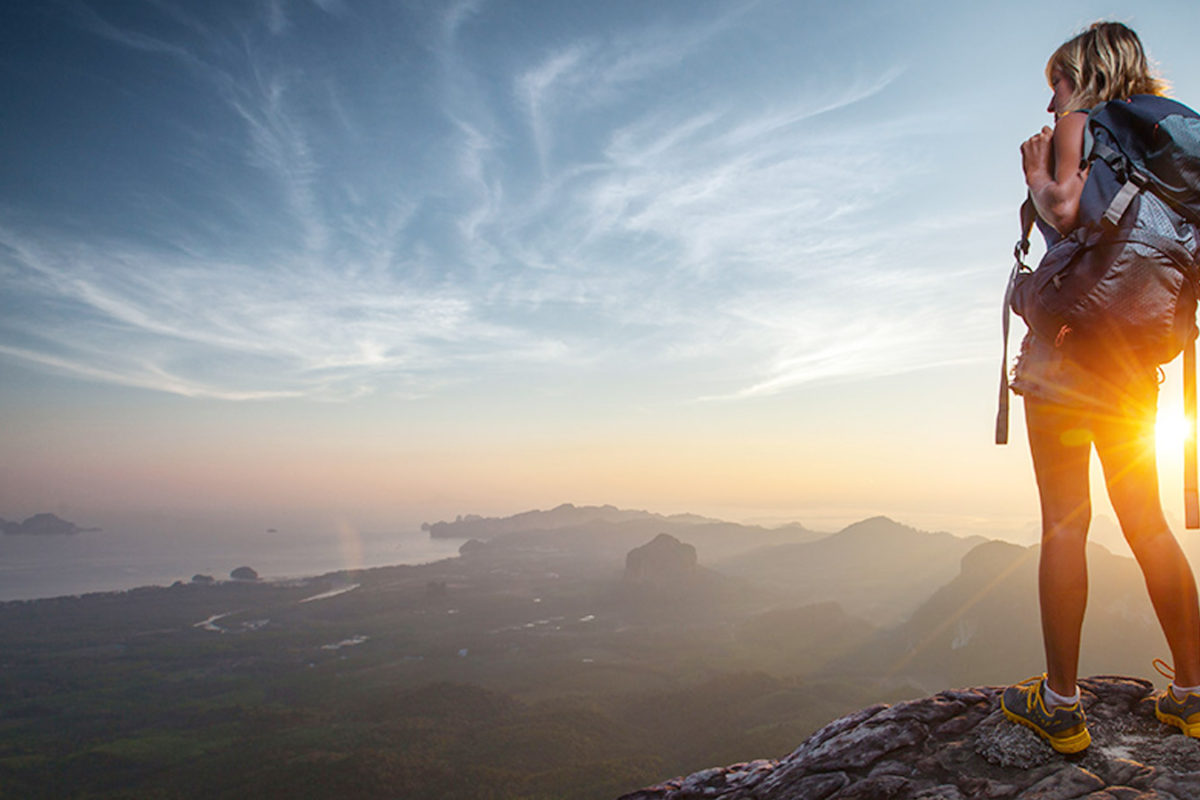 woman standing on a cliff searching for adventure looking for cure for boredom