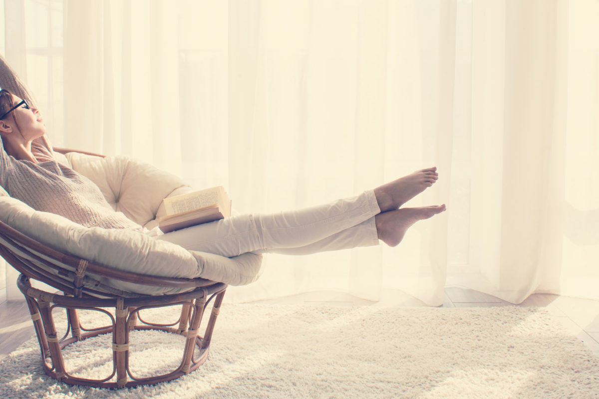woman practicing self-care while stretching in chair with a book on her lap