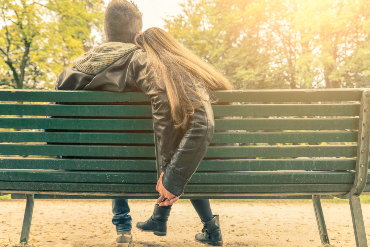 couple sitting on a bench - date night keeping relationships alive