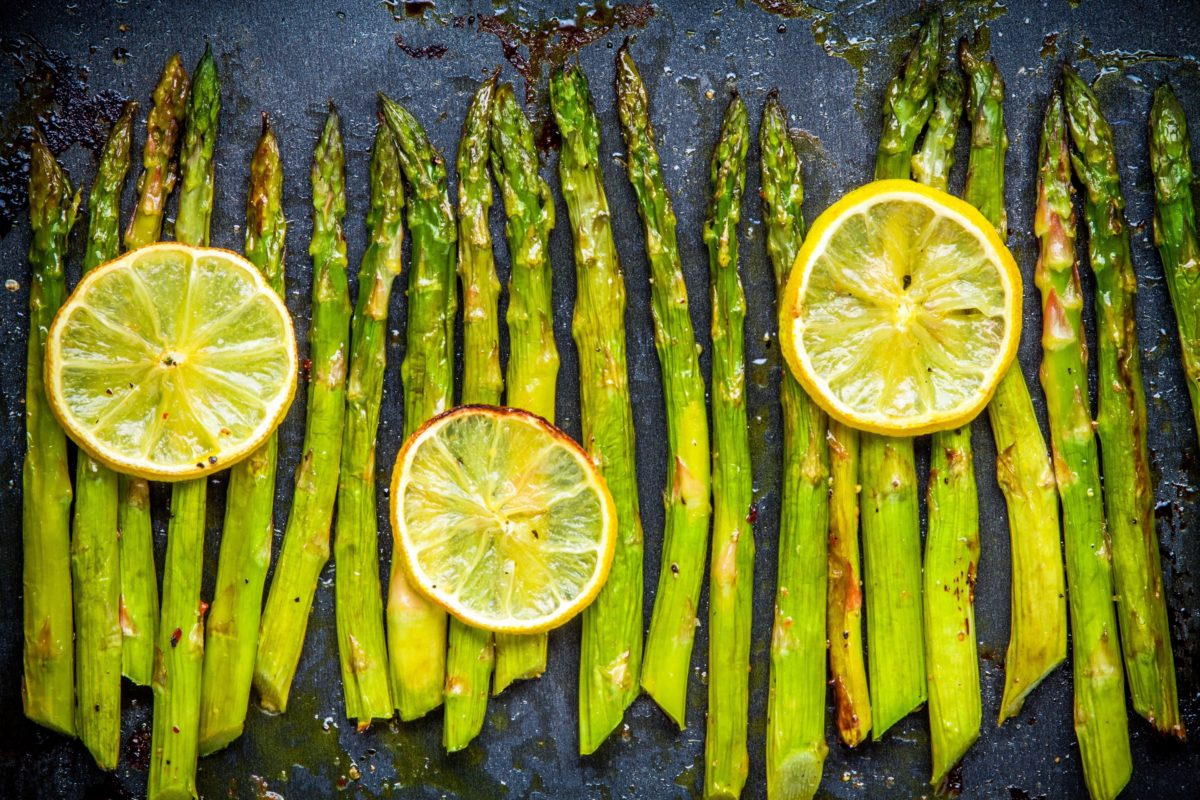 foods that reduce anxiety - baked asparagus with lemon on a dark background