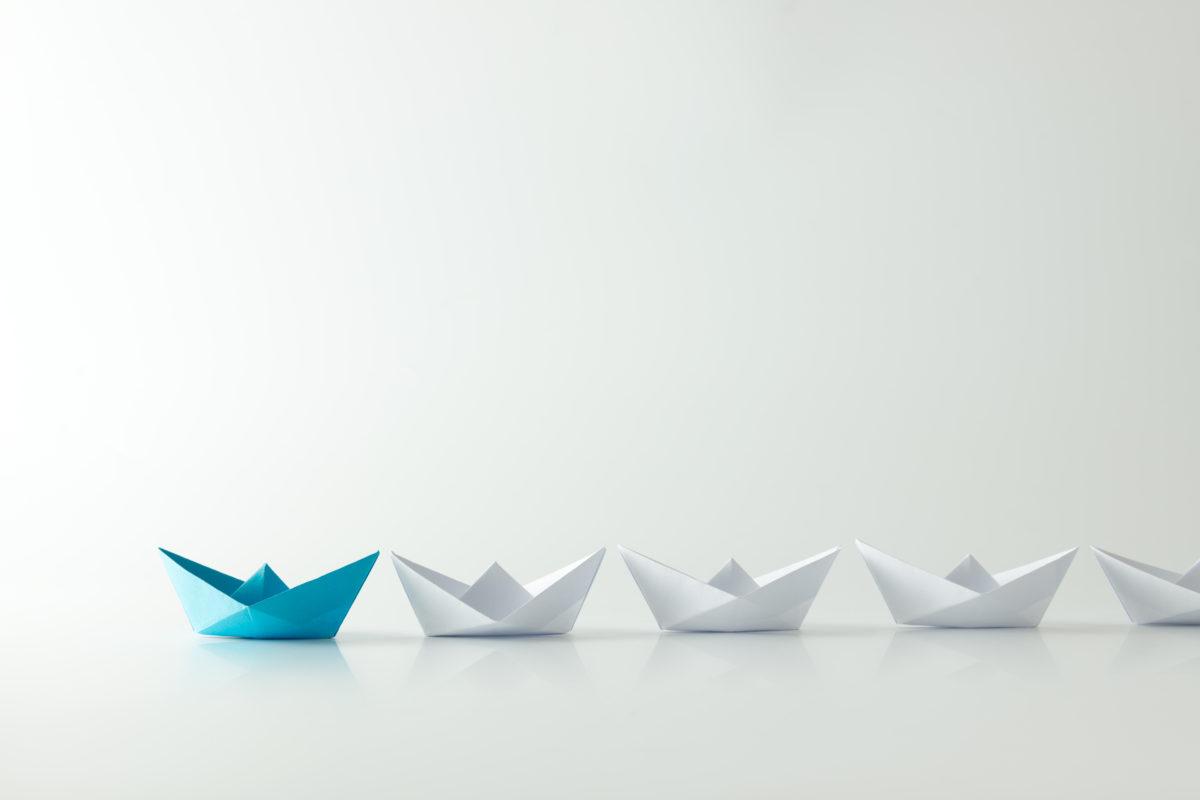 paper origami boats symbolizing a leader