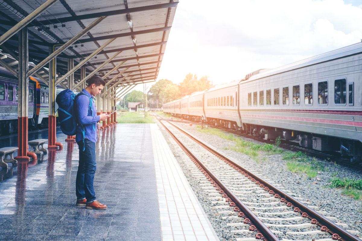 solo traveler man waits train on railway platform