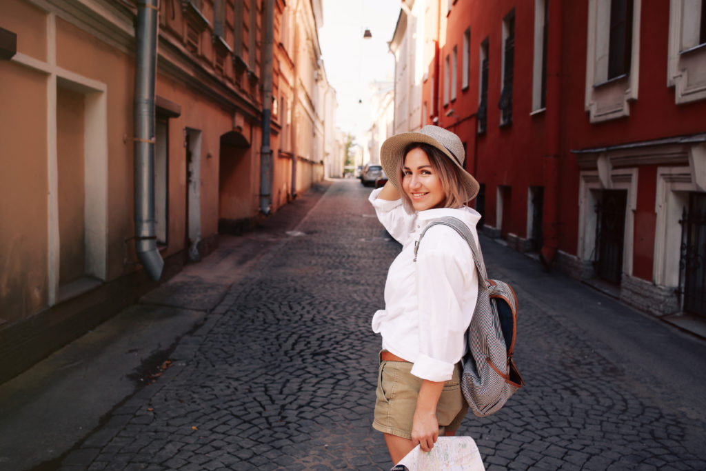 Young female solo traveler with backpack and map on the street.