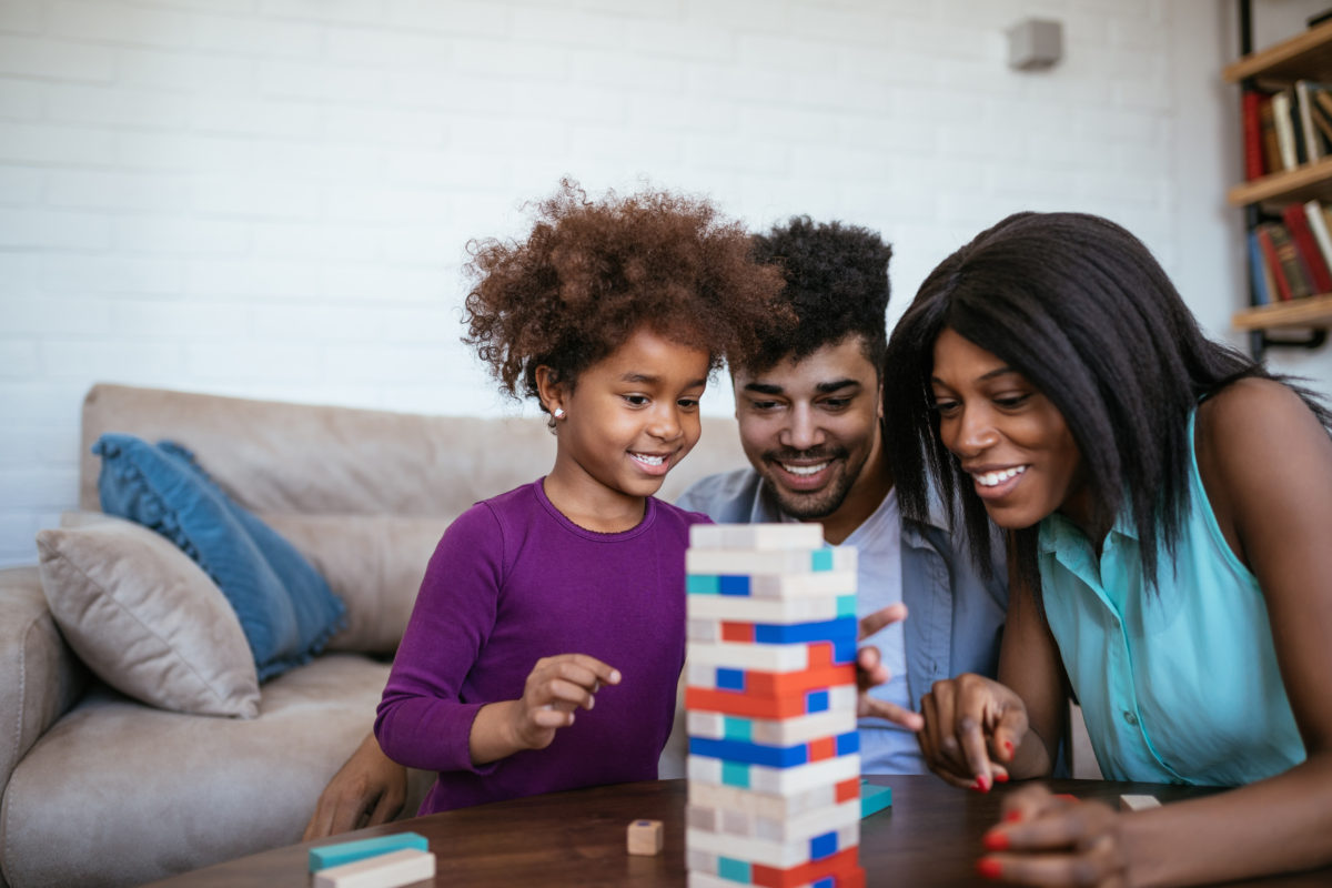 family of 3 playing jenga at the coffee table - family game night