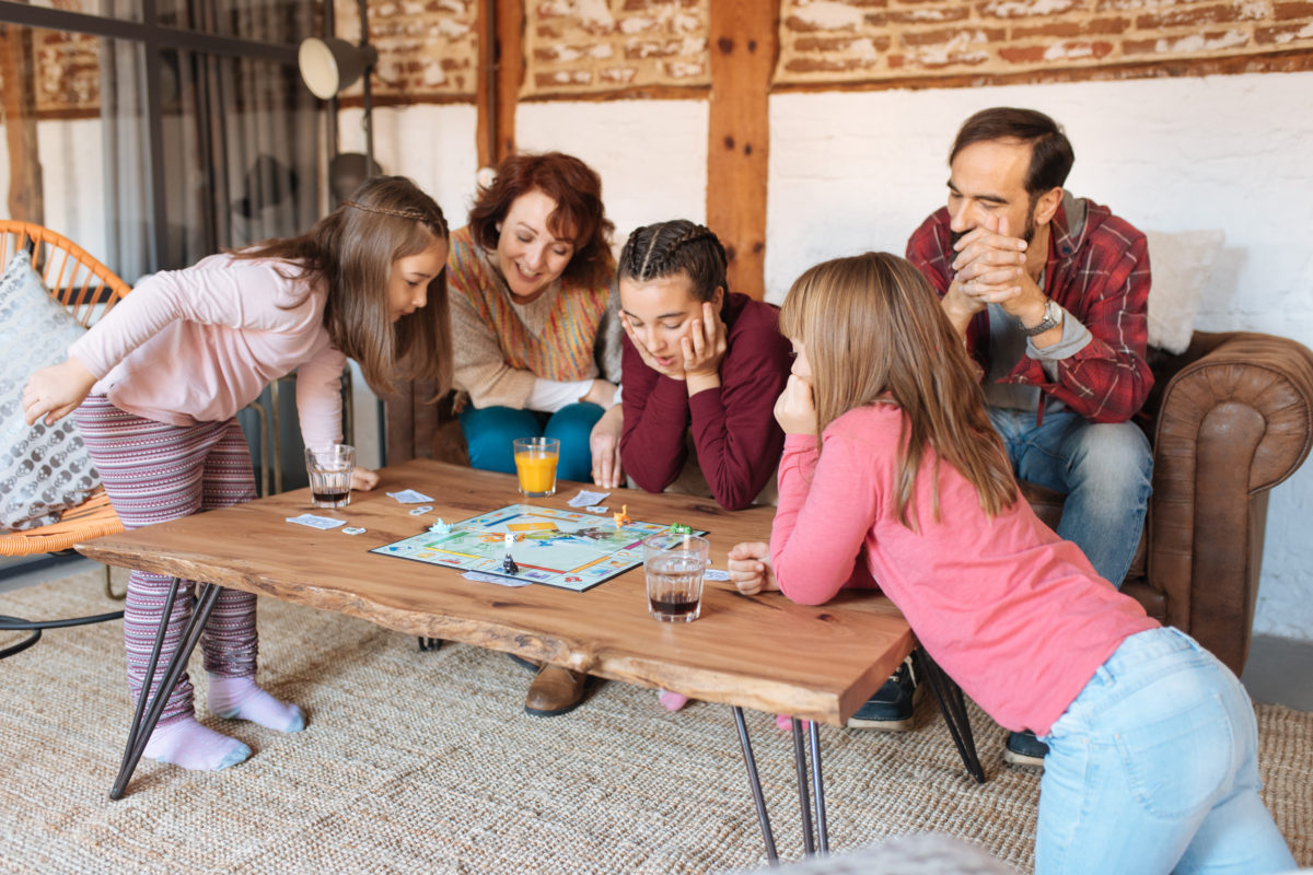 family of 5 playing sorry at the coffee table - family game night