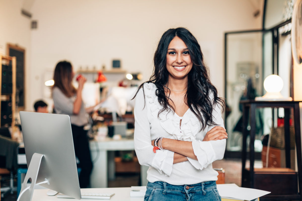 woman standing in front of office, proud of launching a company