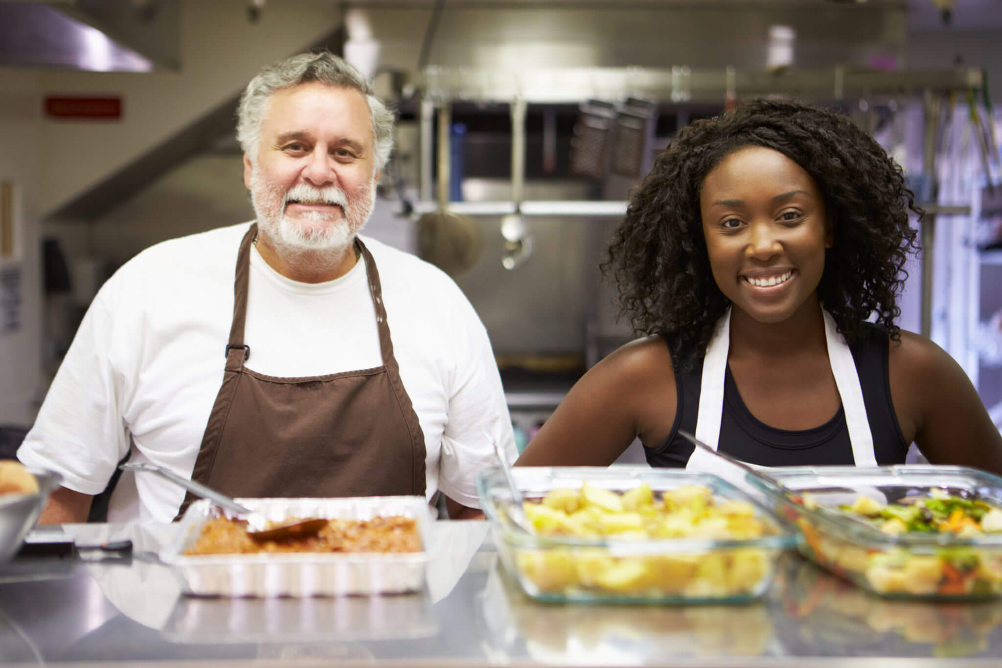 two people volunteering at the local food kitchen to help food relief