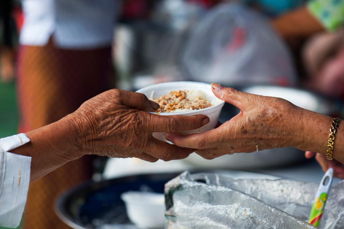 volunteer distributing food at a local food kitchen