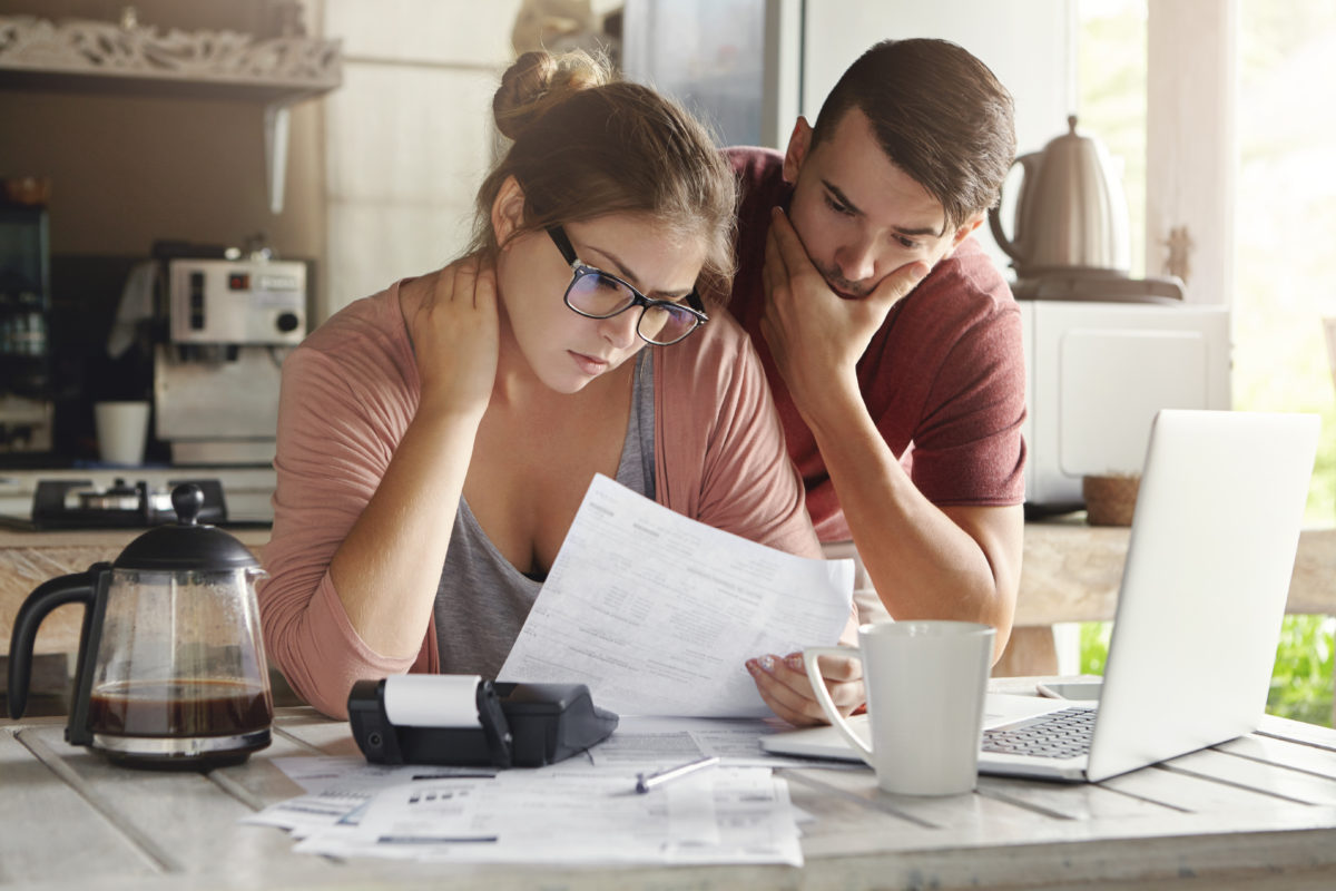 couple discussing finances at computer, saving money in your 30s