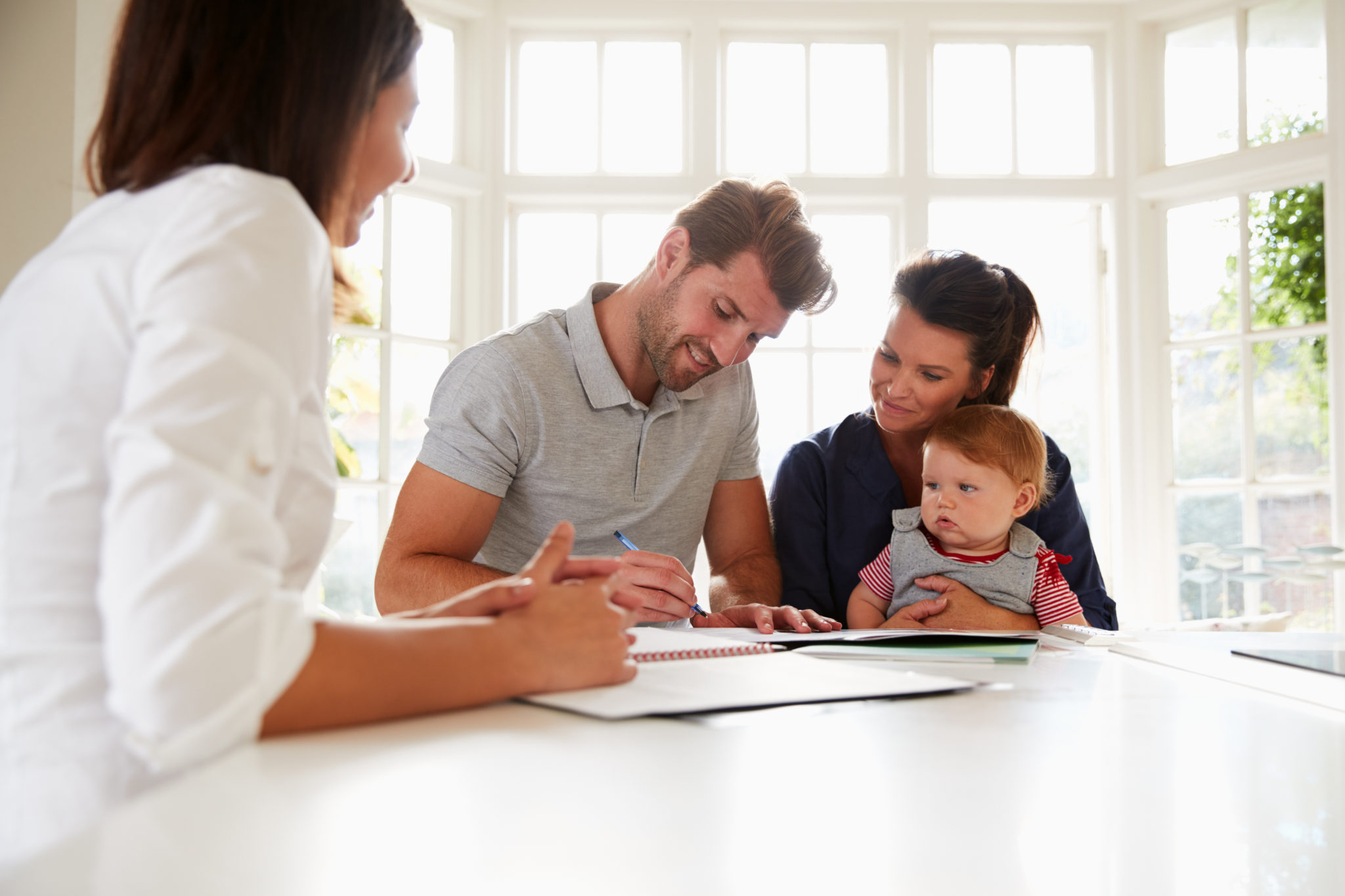 couple with a child talking about finances with their advisor - saving money in your 30s