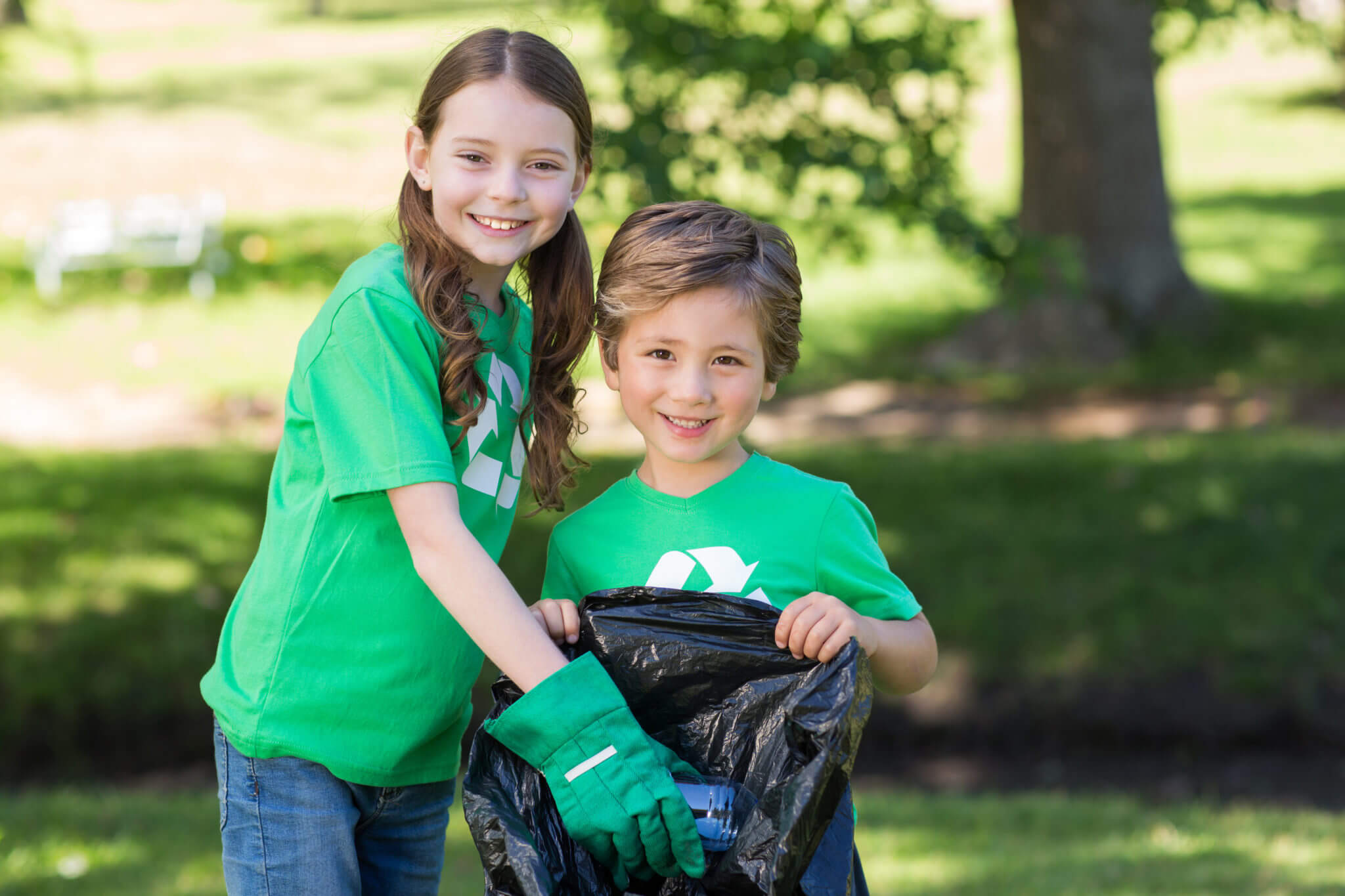 two kids picking up trash demonstrating volunteer opportunities for kids