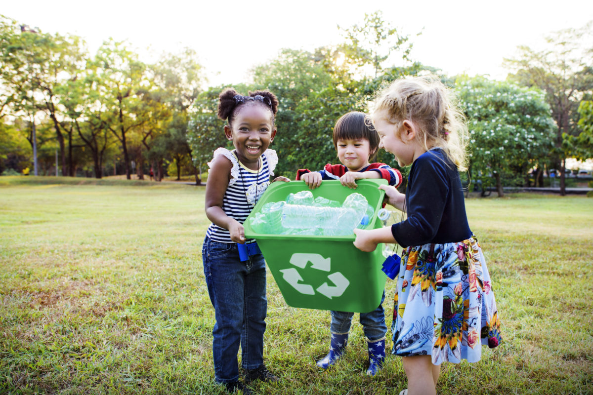 three kids filling a recycling bin demonstrating volunteer opportunities for kids