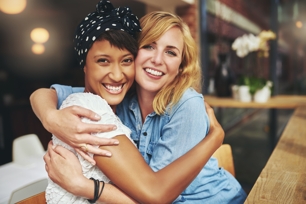 Two woman smiling and hugging