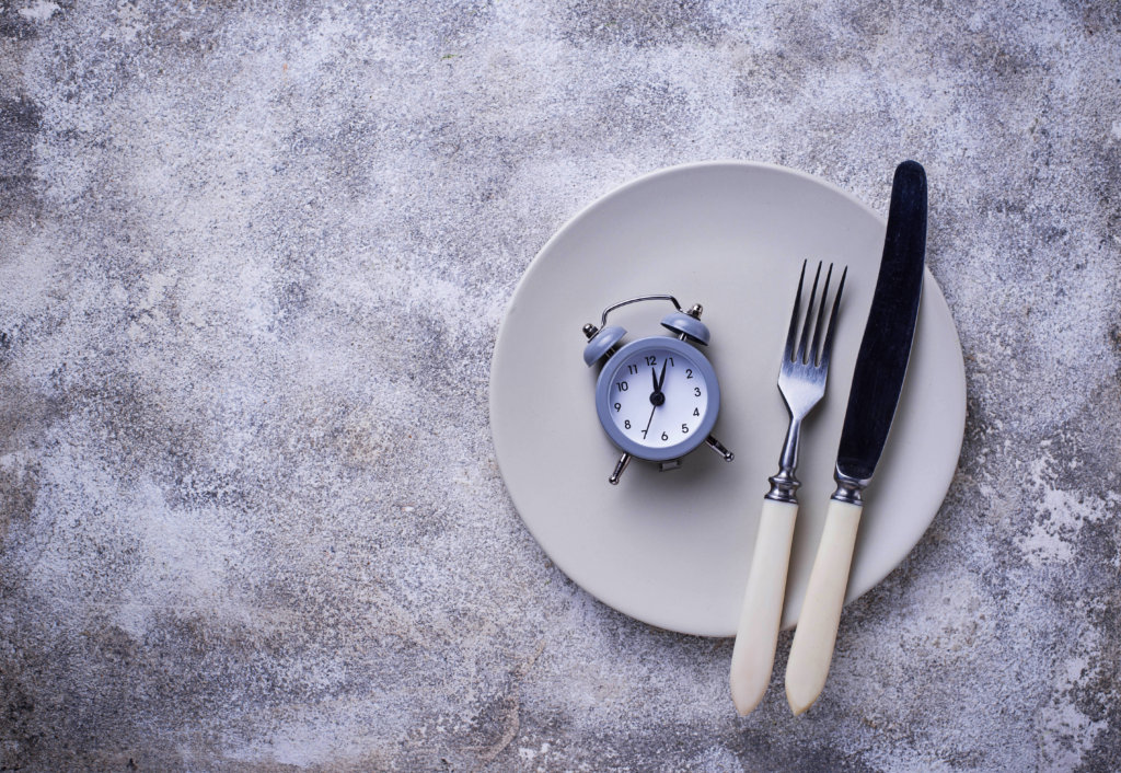 empty plate with clock and utensils illustrating intermittent fasting