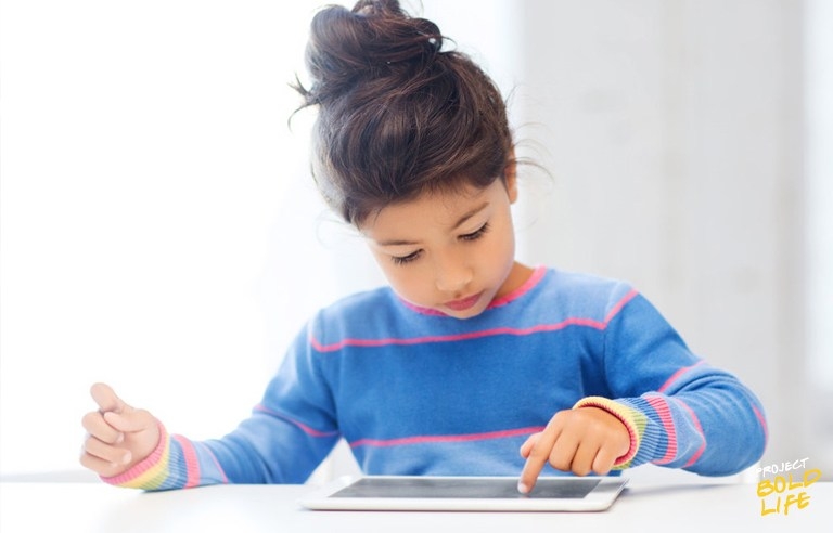 girl in blue sweater navigating her ipad - technology and kids