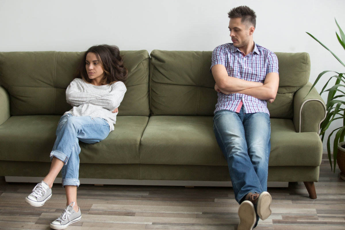 angry man and woman in toxic relationship sitting on couch