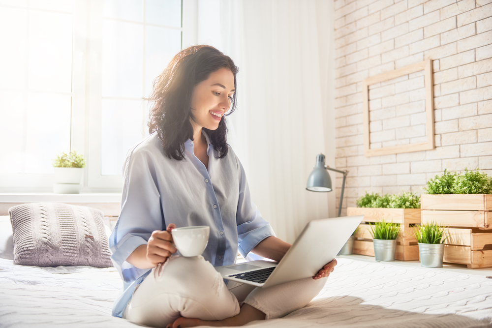 woman on her bed drinking coffee and working from home.