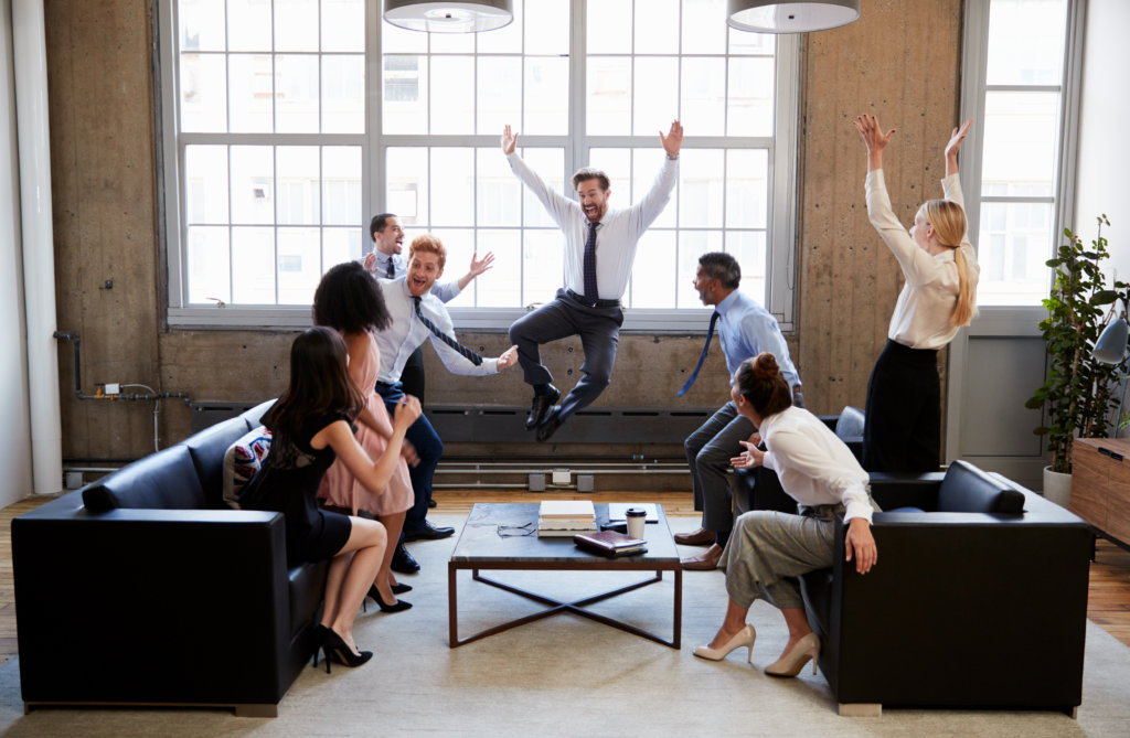 group of motivated coworkers celebrating at work