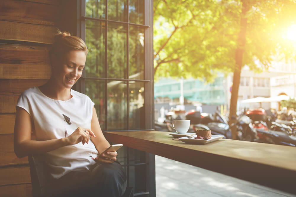 girl sitting at a cafe enjoying her rewards from apps that can make you money