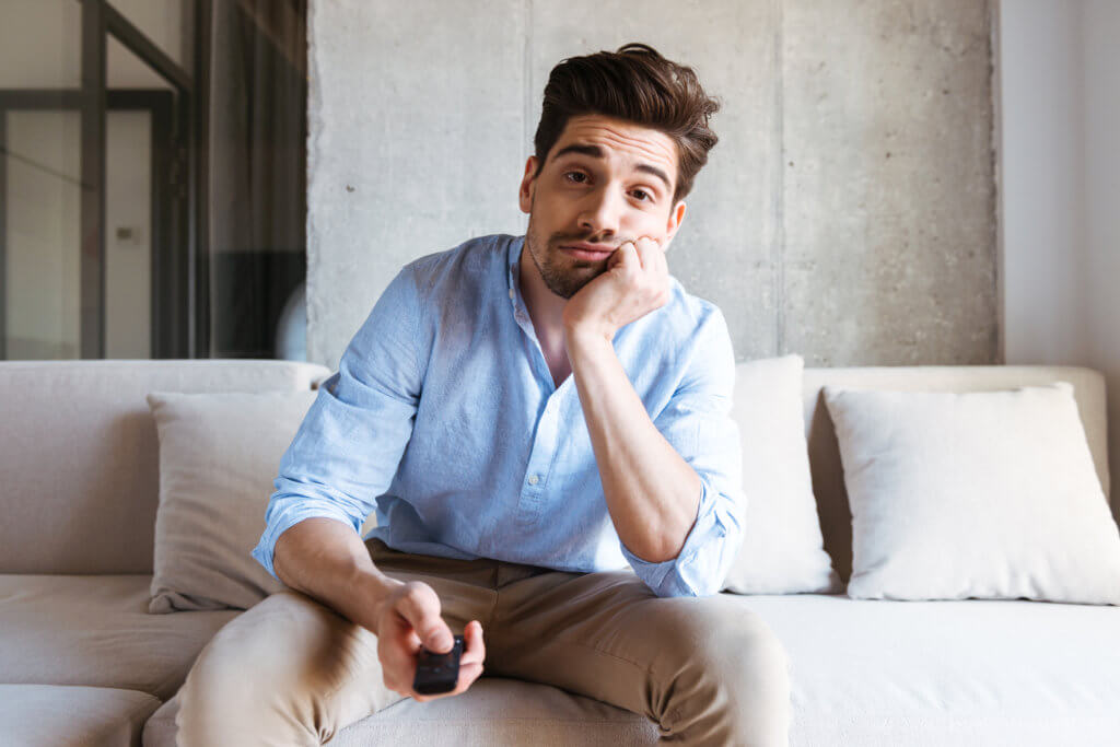 man sitting on a couch watching tv, feeling unmotivated