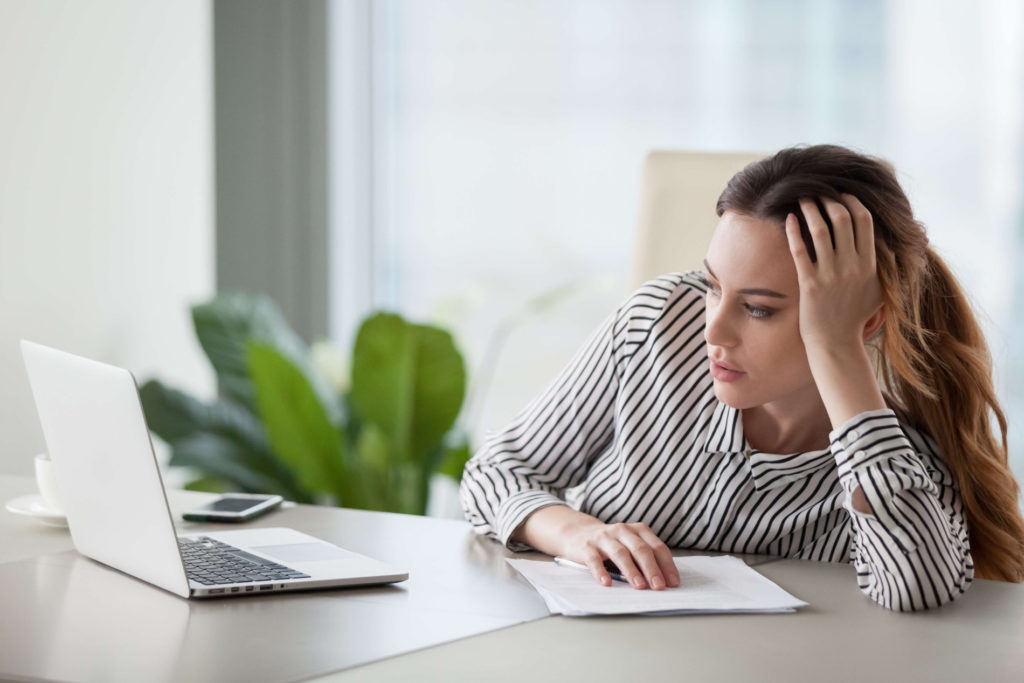 woman staring blankly at her computer feeling unmotivated