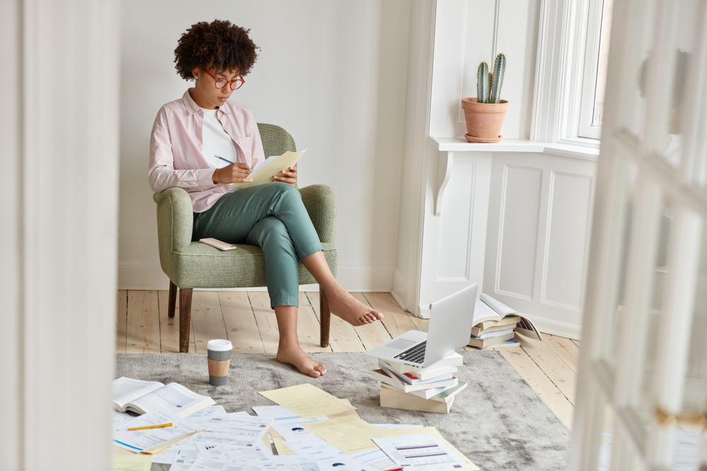 woman sitting in a chair working on her budget to obtain financial independence