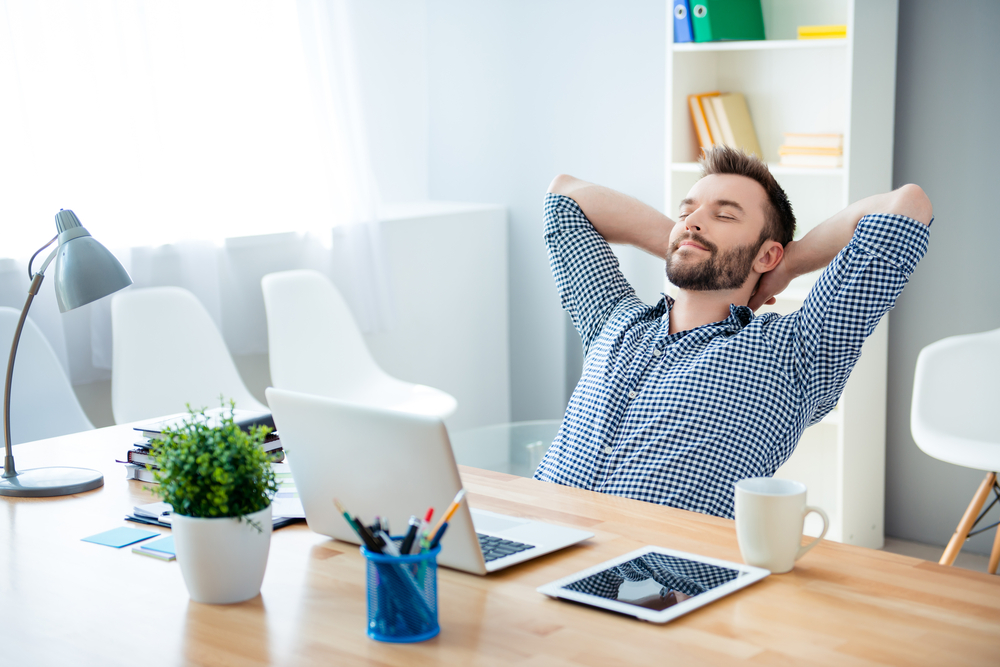 man sitting at desk hands behind his head, happy with his financial independence