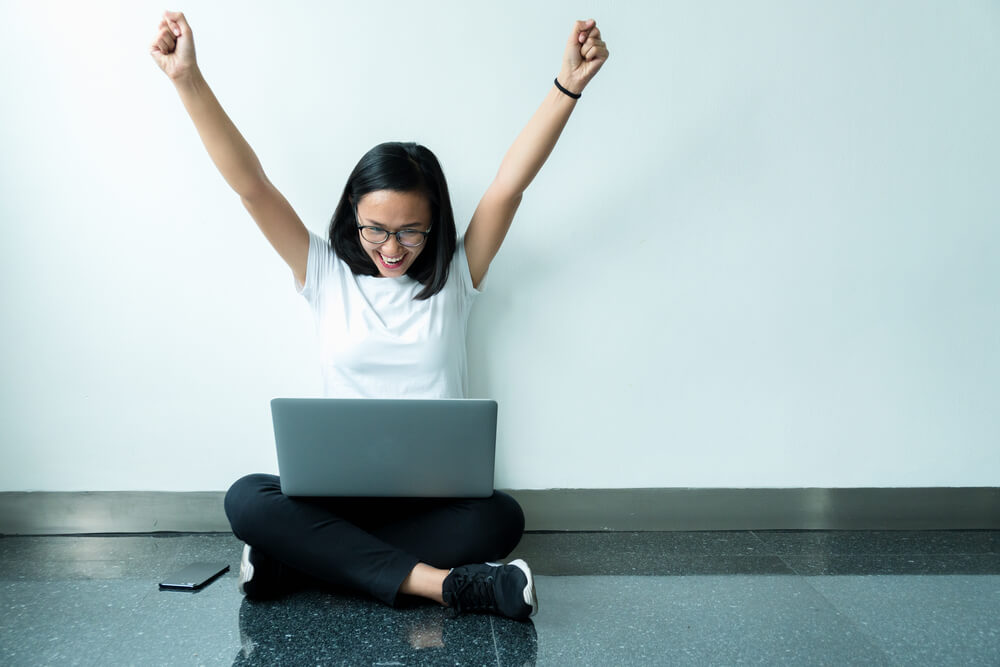 woman celebrating with hands in the air, happy about a new career opportunity