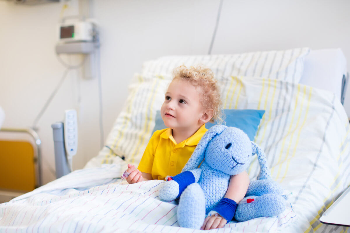 young boy in hospital bed holding a toy provided by toy drive