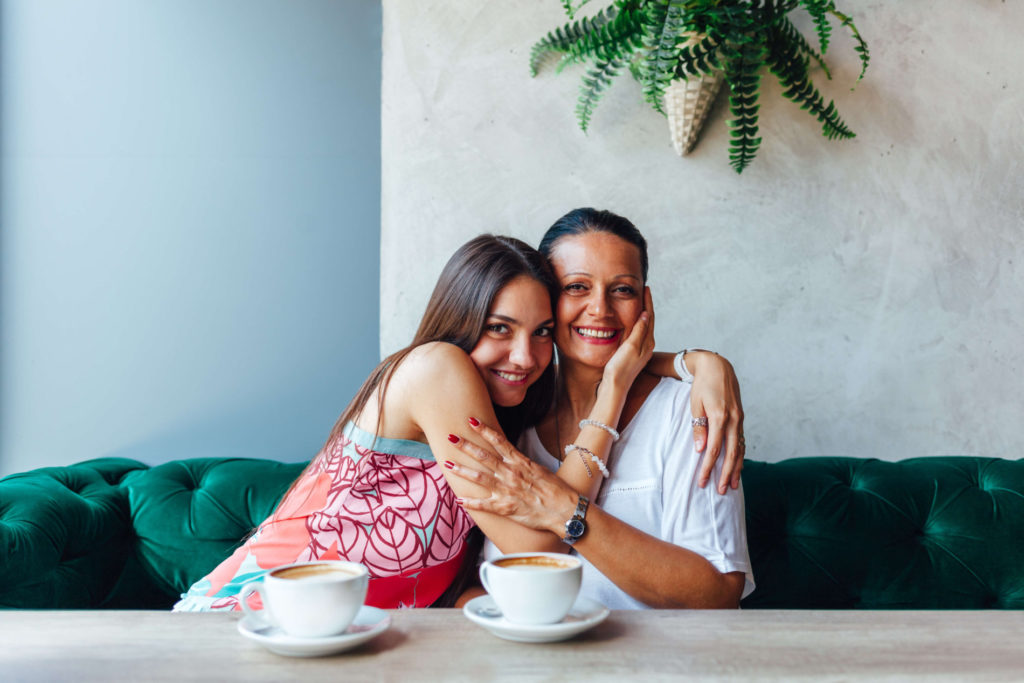 mother and daughter in a cafe hugging