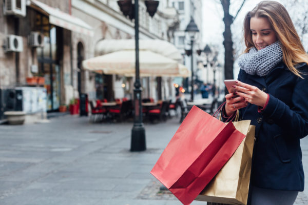 girl outside with shopping bags - save money during the holidays