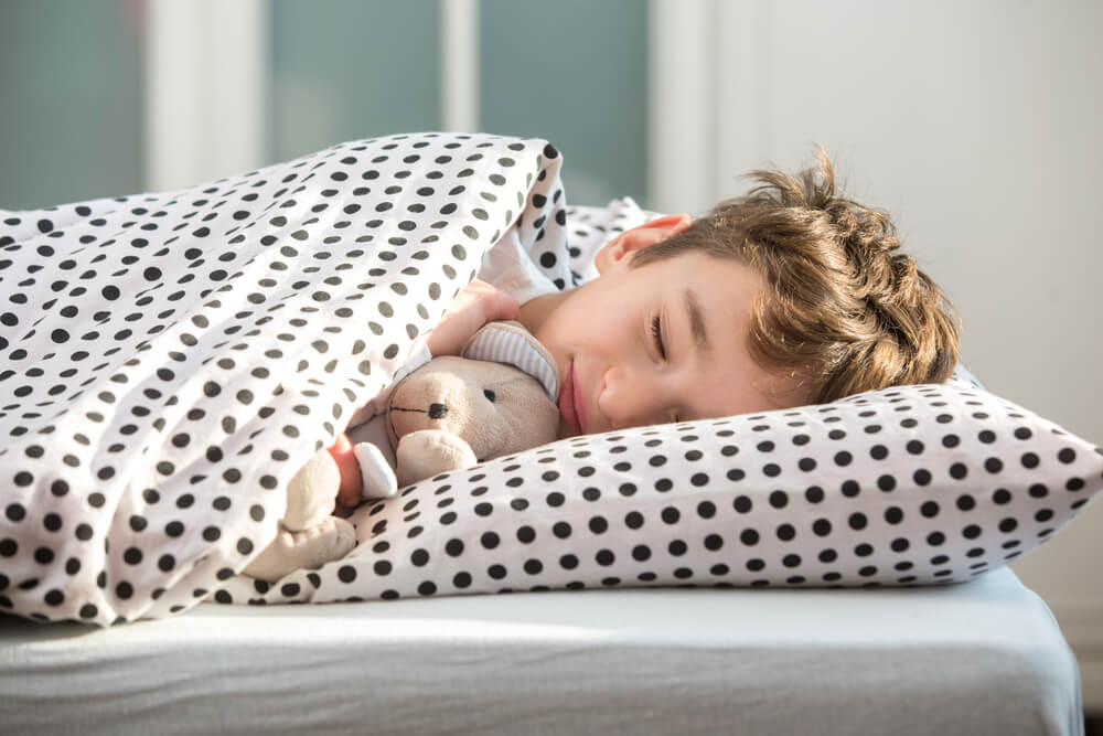 boy sleeping in bed trying to avoid sleep deprivation