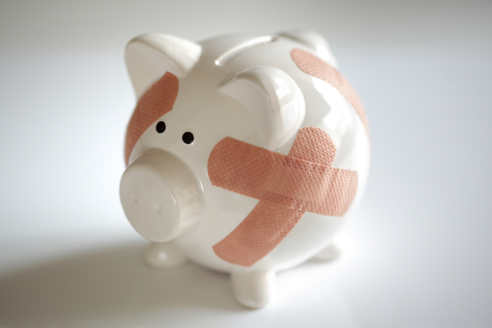 white piggy bank covered in bandaids