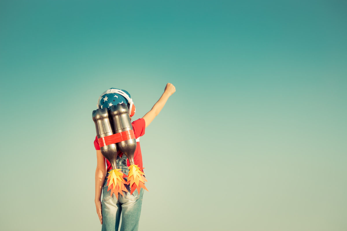 kid with pretend rocket pack on his or her back with arm pointing to the sky - how to harness your inner child