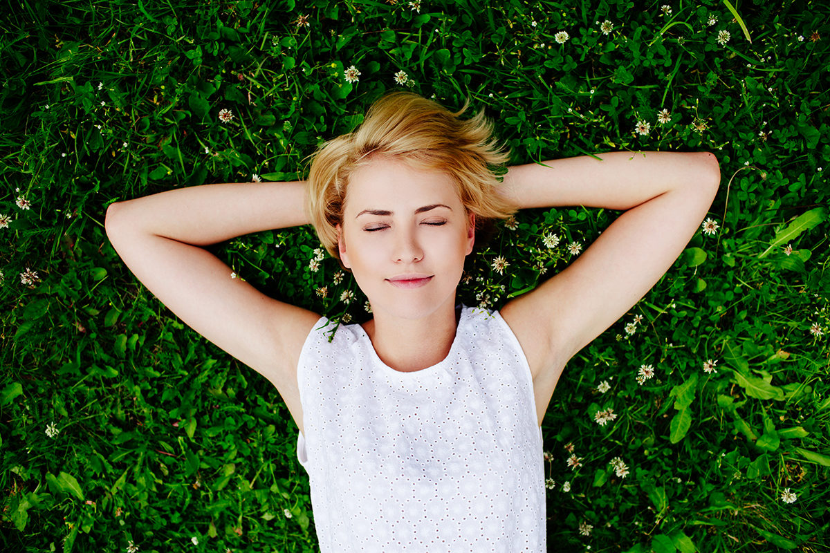girl lying in grass living a happy and healthy life