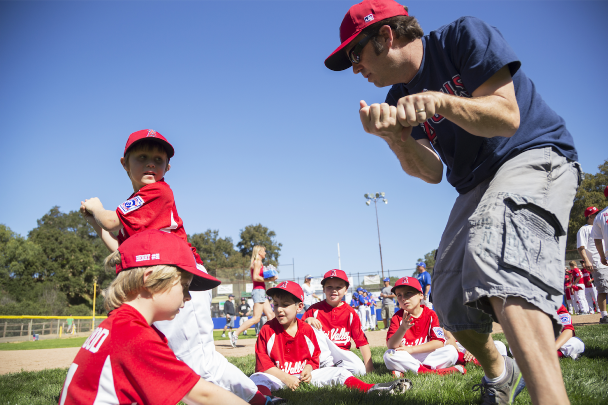 dad volunteering with kids baseball team showing how to swing a bat