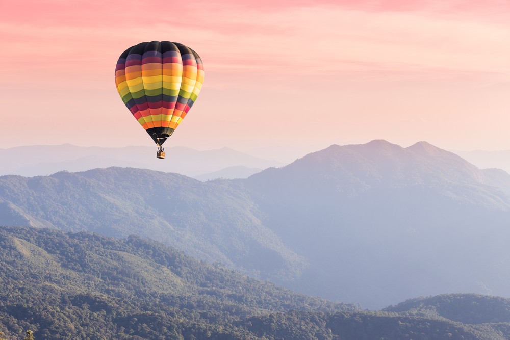 hot air balloon soaring over mountains to symbolize going after success