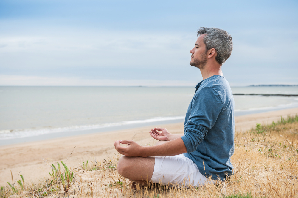 man sitting beachside meditating peacefully