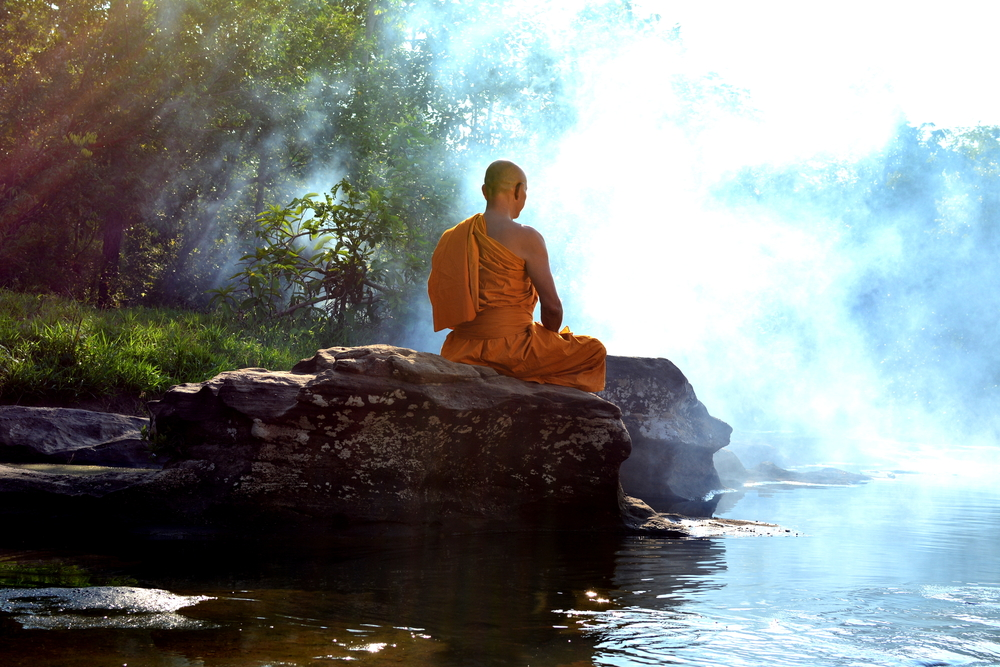 a buddha sitting and meditating on a rock over a body of water