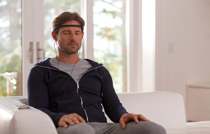 man meditating in chair while using the muse brain sensing headband