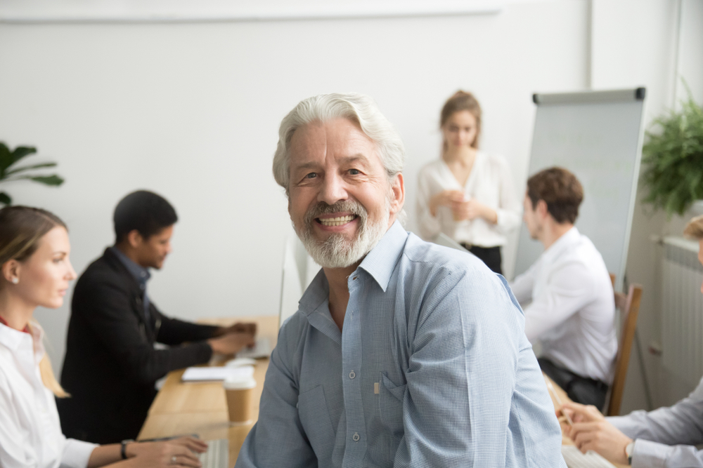 older man in office sitting in front of his team of employees