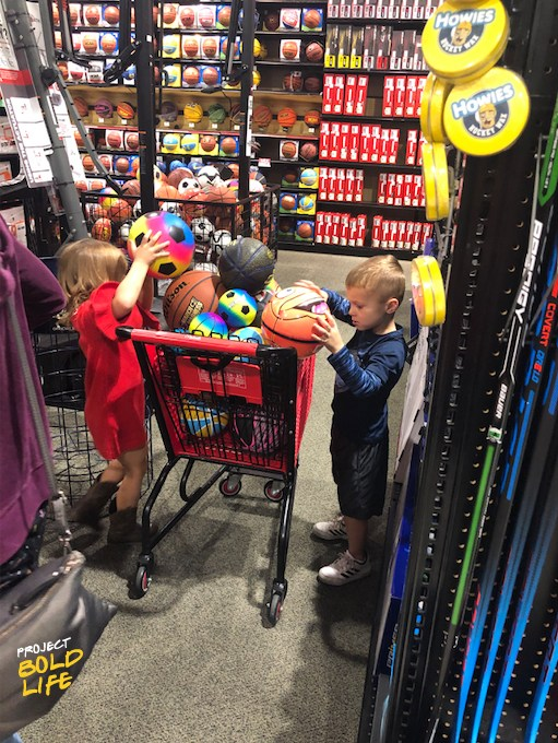 Two Peek family kids add athletic balls to shopping cart