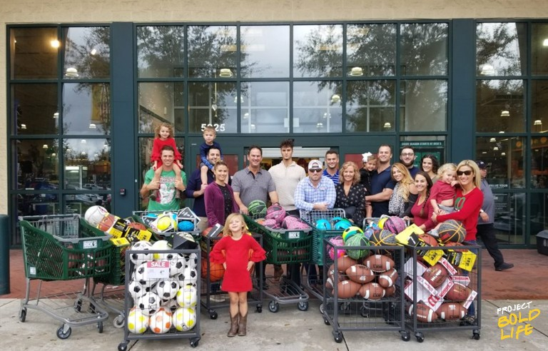 Peek family poses in front of Dick's Sporting Goods with the athletic balls they purchased for donation