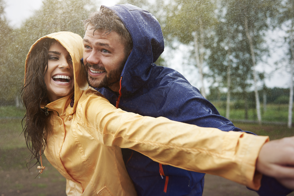 Young couple in rain jackets playing outside in the rain