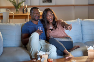 couple enjoying date night at home with wine and a movie